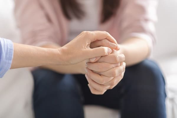 Close up of therapist touching woman patient hands