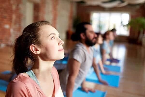 group-of-people-doing-yoga-cobra-pose-at-studio