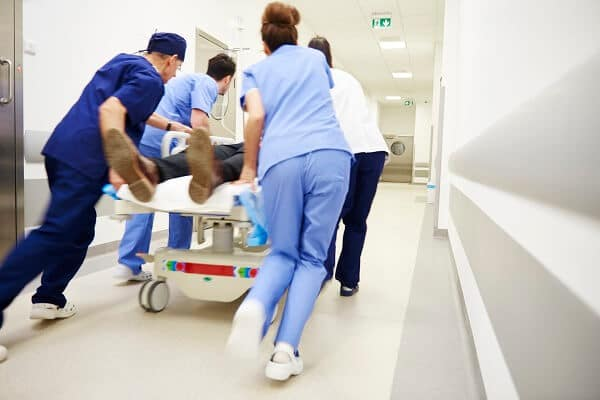 health care workers running emergency patient